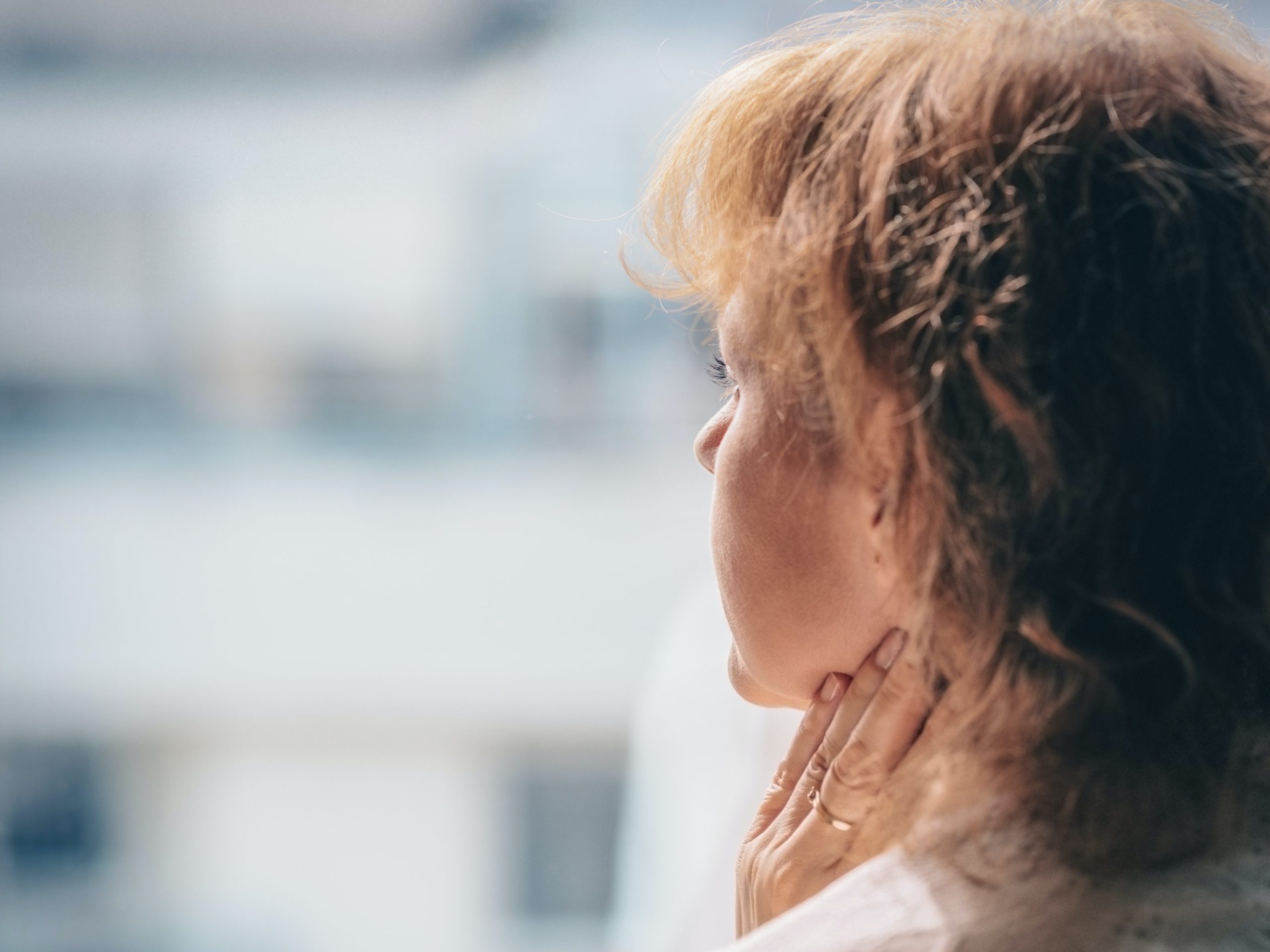 Woman staring into the distance with fingers on her neck