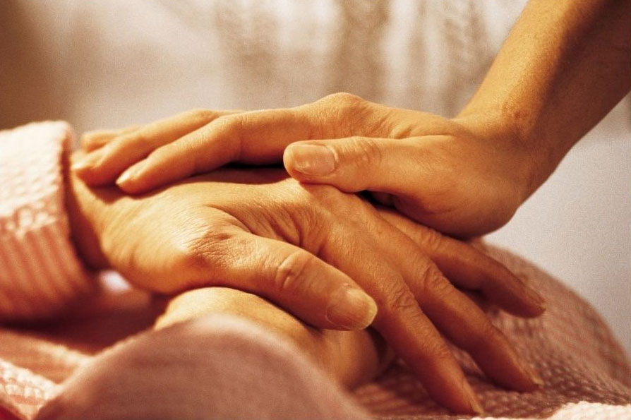 Hand of caregiver on top of the hand of a senior